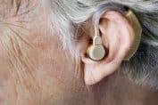 Personne âgée souffrant de surdité équipée d'un appareil auditif pour mieux entendre