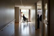 Infirmière en maison de retraite qui accompagne un résident en fauteuil roulant