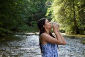 Jeune femme qui boit un verre d'eau au pied d'une source pour ses bienfaits sur la santé