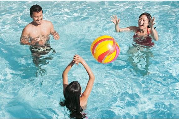 2 adultes et un enfant jouant au ballon dans une piscine