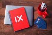 objets publicitaires carnet rouge posé sur odinateur portable stylos dans un pot rouge et cartes de visites