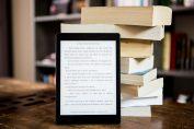 Liseuse électronique à côté d'une pile de livres