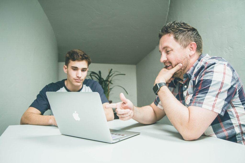 deux hommes devant un ordinateur