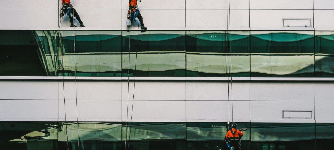 3 personnes nettoyant les vitres d'un immeuble en rappel