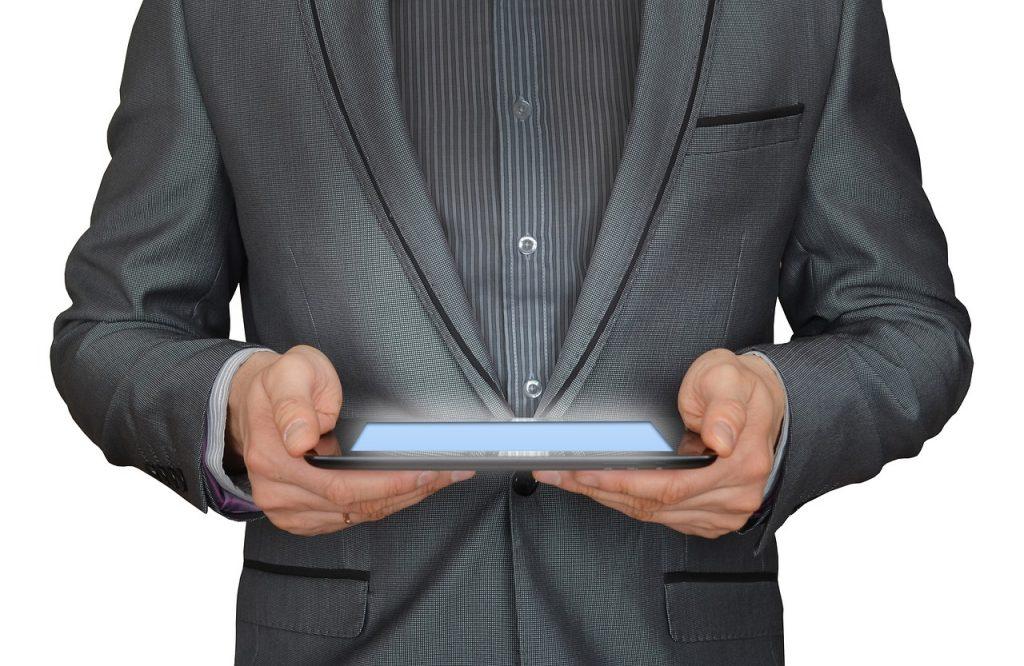 homme en costume qui tient une tablette numérique