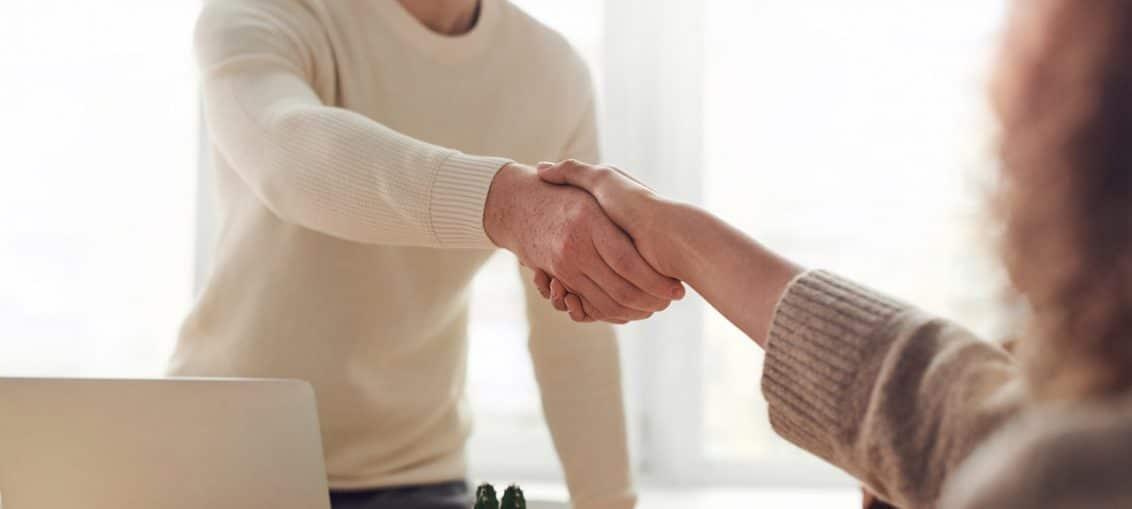 personne debout qui serre la main d'une personne assise